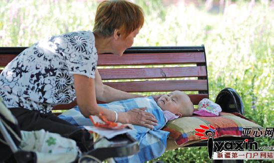 7月15日10时34分,乌市气温达到36℃,一位市民带着年幼的孩子来到乌市植物园避暑纳凉。亚心网记者马元摄